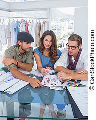 Three fashion designers during a brainstorming in a bright...