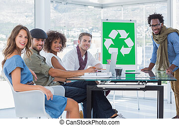 Young designers during a meeting with recycle symbol on...