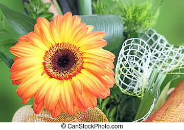 fresh flower bouquet with orange gerbera and green leaves