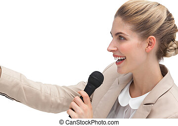 Side view of businesswoman with microphone and hand raised