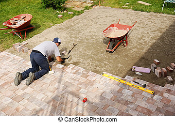 Man laying down paver - Young man installing paver bricks...
