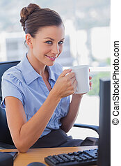 Businesswoman holding coffee mug and smiling in the office