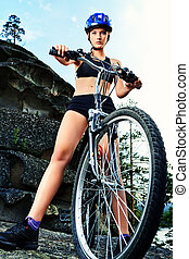 altitude - Active young woman rides a bike in the mountains.