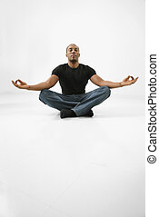 Man sitting meditating - African American young male adult...