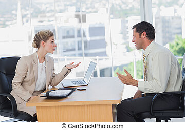 Businesswoman interviewing a smiling businessman in office