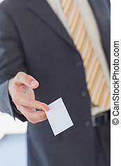 Businessman giving a white blank business card in office