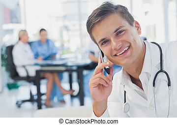 Smiling doctor calling while his colleagues are in a meeting