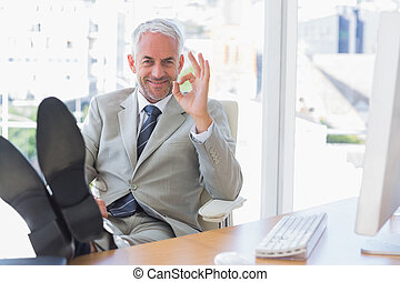 Happy businessman giving ok sign with feet up on his desk