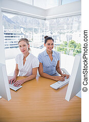 Happy businesswomen working side by side at a desk in office