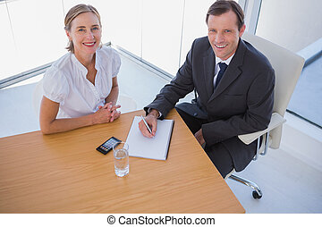 Overhead of smiling business people taking notes in their...