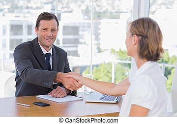 Smiling businessman shaking hand of a job applicant in his...