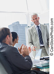 Colleagues applauding the manager during a meeting in the...
