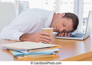 Businessman sleeping on a laptop while he is holding a cup...