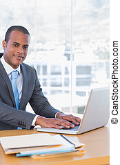 Happy businessman working on his laptop in his office
