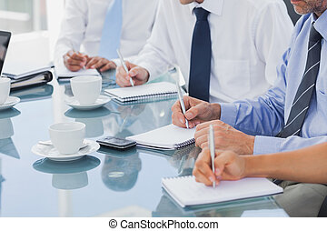 Business people taking notes on notepads during a meeting