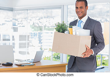 Smiling businessman leaving his company as he has been fired
