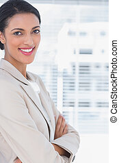 Cheerful businesswoman with arms crossed