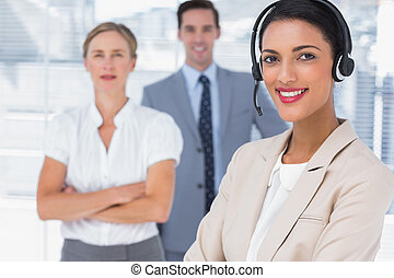 Attractive woman with headset crossing her arms in front of...