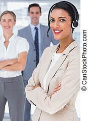 Smiling businesswoman with headset crossing her arms in...