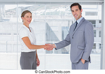 Two colleagues shaking hands in the office
