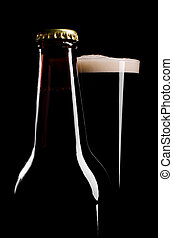 Dark ale - The closed beer bottle and full glass of dark...