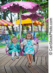 Two little fashion lovely sisters ride on the carousel in the park