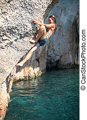 Deep water soloing, female climber on cliff - Deep water...
