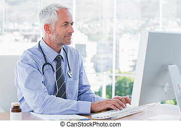 Doctor typing on his computer