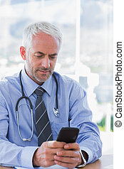 Doctor typing a text message on his smartphone - Attractive...