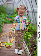 Little girl holds the crop onions in the greenhouse