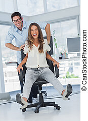 Cheerful designers having fun with a swivel chair in their...