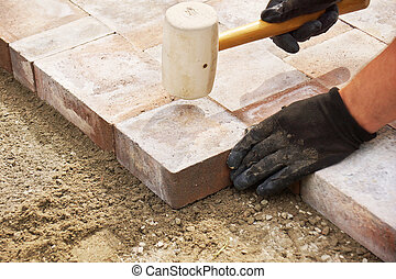 Using a mallet to set paver - Installing paver bricks on...