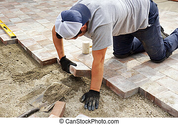 Laying down paver - Worker installer paver bricks on large...