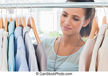 Attractive fashion woman looking at clothes in a studio