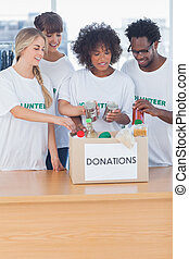 Volunteers putting food in donation box in their office