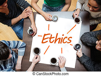 Team brainstorming over a poster with ethics written on it -...