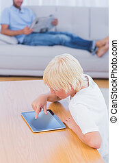 Boy using tablet at table in the living room