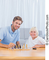 Smiling father playing chess with his son in the living room