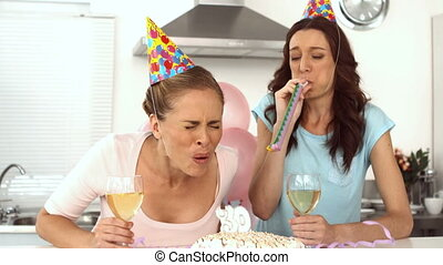 Woman blowing candle and celebrating her birthday with a...