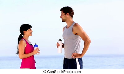 Man and woman drinking water on the beach after sport