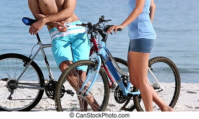 Friends laughing and holding bikes on the beach