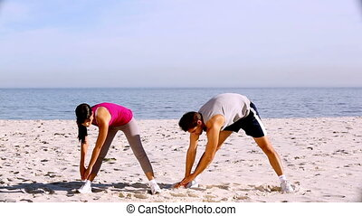 Sportsman and sportswoman stretching together on the beach