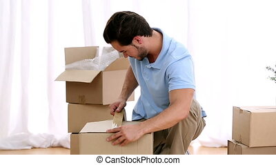 Man closing a moving box and getting ready for move