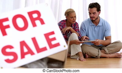 Couple sitting on floor using digital tablet in their empty...