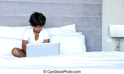 Child using laptop in bedroom - Child sitting on bed and...