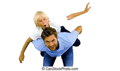 Son having a piggy back on his father on white background in...