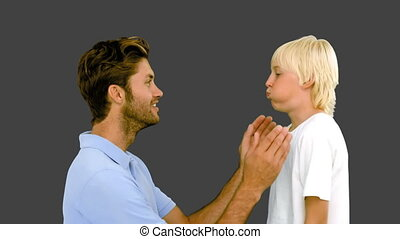 Man pressing inflated cheeks of his son on grey background...
