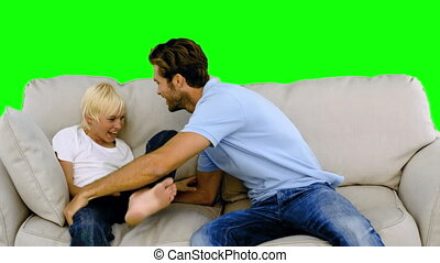 Father tickling his son on the sofa on green screen in slow...