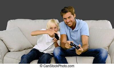 Father and son playing video games on grey background in...
