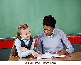 Schoolgirl Asking Question To Teacher At Desk - Little...